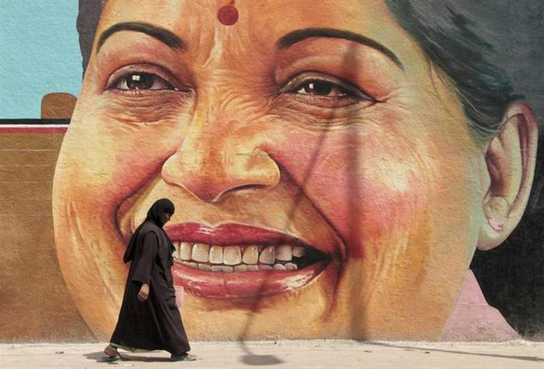 A woman walks past a portrait of J. Jayalalithaa, chief minister of Tamil Nadu, in Chennai March 13, 2012. REUTERS/Babu/Files