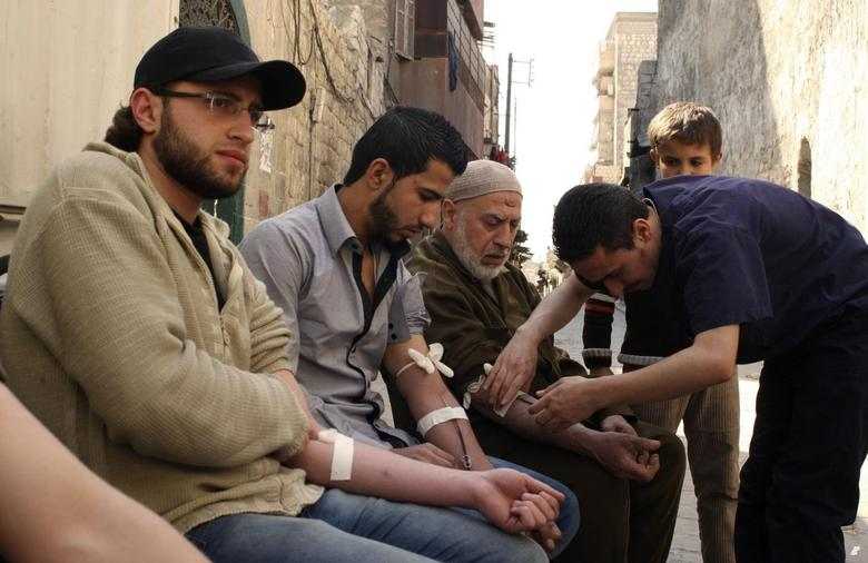 Men donate blood during a campaign to supply blood to field hospitals in Aleppo March 23, 2014. REUTERS/Abdalrhman Ismail