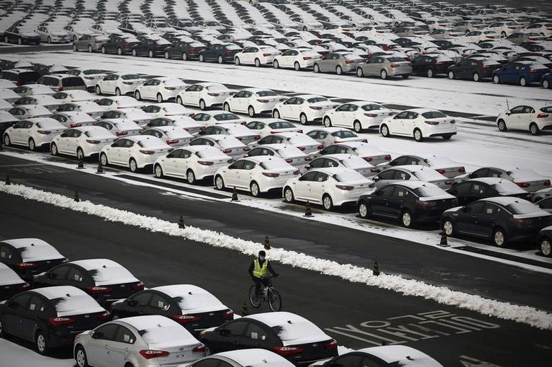 A worker cycles past cars made by South Korea's automakers Hyundai Motor and affiliate Kia Motors parked at the company's shipping yard at a port in Pyeongtaek, about 70 km (43 miles) south of Seoul January 20, 2014. REUTERS/Kim Hong-Ji