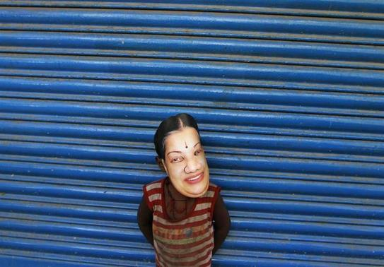 A boy wears a mask of J. Jayalalithaa, chief minister of Tamil Nadu state and chief of Anna Dravida Munetra Khazhgam (AIADMK), during an election campaign ahead of the general elections in Chennai March 21, 2014. REUTERS/Babu