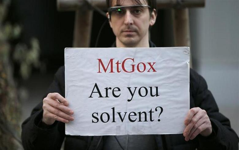 Protester Aaron holds a placard during a demonstration against Mt. Gox, in front of the building where the digital marketplace operator is housed, in Tokyo February 25, 2014. REUTERS/Toru Hanai/Files