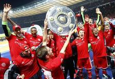 """Игроки """"Баварии"""" радуются завоеванию чемпионского титула в Германии в Берлине 25 марта 2014 года. Мюнхенская """"Бавария"""" рекордно быстро завоевала чемпионский титул в немецкой Бундеслиге, во вторник обыграв берлинскую """"Герту"""" со счетом 3-1. REUTERS/Kai Pfaffenbach"""