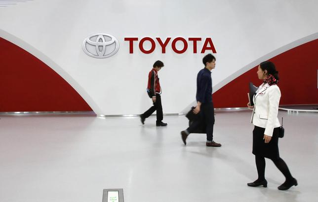 Employees and a customer (C) walk in front of Toyota Motor's logo at the company's showroom in Tokyo March 12, 2014. REUTERS/Toru Hanai