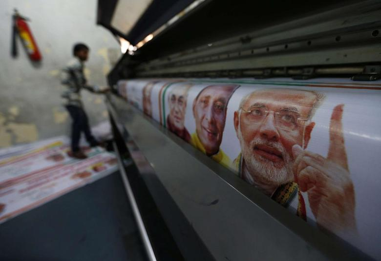 A worker operates a machine to print banners of Hindu nationalist Narendra Modi (R), prime ministerial candidate for India's main opposition Bharatiya Janata Party (BJP), along with other leaders of the party ahead of the general elections in Ghaziabad, on the outskirts of New Delhi, March 24, 2014. REUTERS/Adnan Abidi