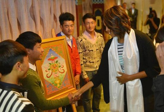 U.S. first lady Michelle Obama (R) greets Tibetan students after arriving at a Tibetan restaurant for lunch in Chengdu, in China's Sichuan province, March 26, 2014. REUTERS/Peter Parks/Pool