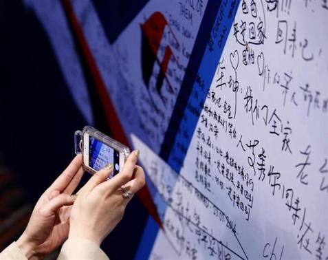 A female journalist takes a picture of a message board with messages wishing the return of passengers aboard Malaysia Airlines MH370 at the Lido Hotel in Beijing March 26, 2014. REUTERS/Kim Kyung-Hoon