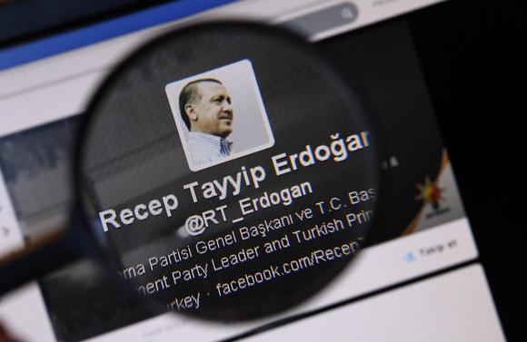 An image of Turkish Prime Minister Tayyip Erdogan on a twitter account is pictured through a magnifying glass in this illustration picture taken in Istanbul March 21, 2014. REUTERS/Murad Sezer
