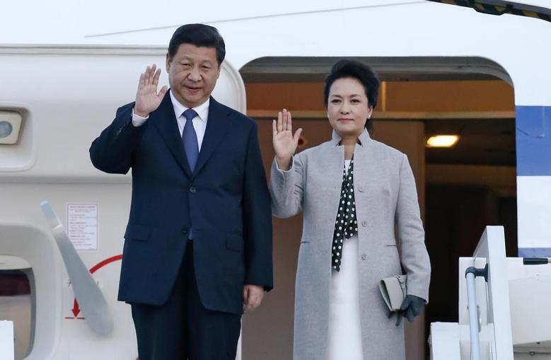 China's President Xi Jinping (L) and his wife Peng Liyuan wave as they arrive at the Lyon-Saint-Exupery airport in Colombier-Saugnieu, near Lyon, March 25, 2014. REUTERS/Robert Pratta