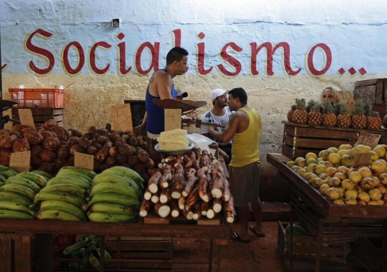 Vendors wait for customers at their stalls, with prices tagged in Cuban pesos, at a market in Havana October 23, 2013. REUTERS/Desmond Boylan
