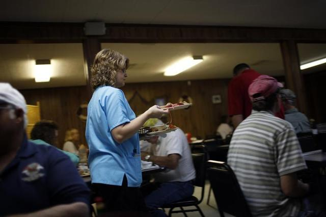 A waitress carries plates at a seafood restaurant in a file photo. REUTERS/Carlos Barria