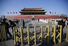 Security guards set up a fence in front of the portrait of China's late leader Mao Zedong at the main entrance of the Forbidden City near the Great Hall of the People where the National People's Congress (NPC) is taking place in Beijing March 6, 2014. REUTERS/Kim Kyung-Hoon