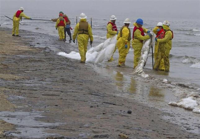 Workers place oil absorbent booms and snares on the east end of Galveston Island March 24, 2014. REUTERS/Richard Carson