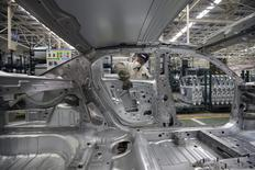 An employee installs car doors at a production line of Dongfeng Peugeot Citroen Automobile factory in Wuhan, Hubei province, February 13, 2014. REUTERS/Darley Shen