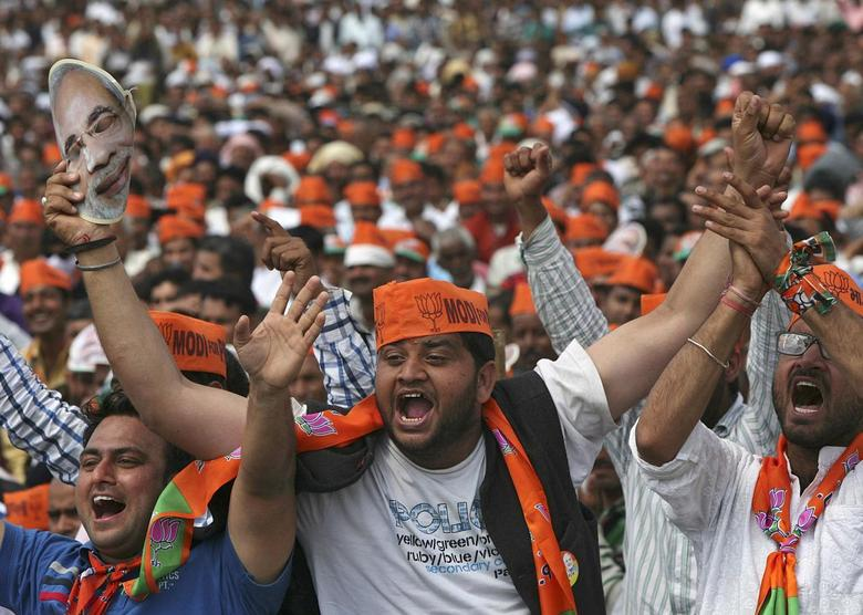 Supporters of Hindu nationalist Narendra Modi, prime ministerial candidate for India's main opposition Bharatiya Janata Party (BJP) and Gujarat's chief minister, cheer as they listen to Modi during a rally in Hiranagar March 26, 2014. REUTERS/Mukesh Gupta