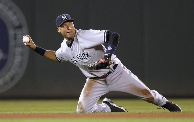 New York Yankees shortstop Derek Jeter cannot throw out Minnesota Twins' Jamey Carroll at first base during the seventh inning of their American League MLB baseball game at Target Field in Minneapolis, September 25, 2012. REUTERS/Eric Miller