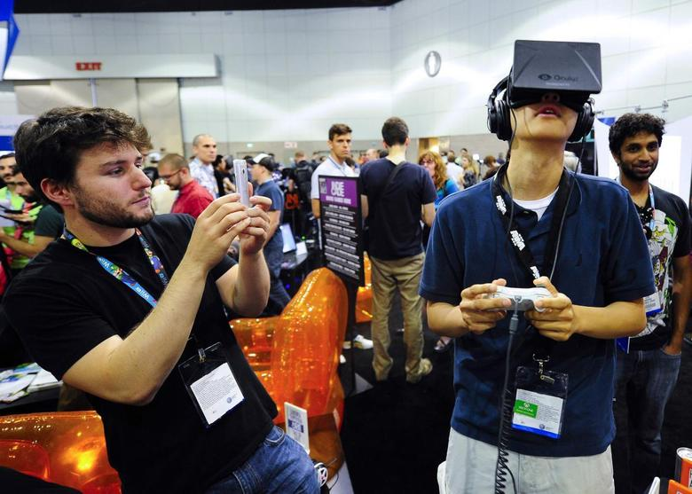 Software designer Julian Kantor (L), who created ''The Recital'', takes a picture of Jonathan Feng using the Oculus Rift virtual reality headset to experience his program during E3 in Los Angeles, California in this June 12, 2013 file photo. REUTERS/Gus Ruelas/Files