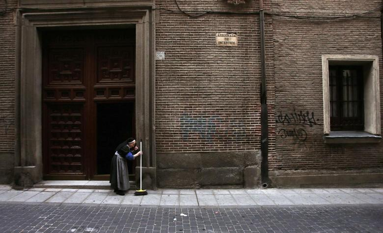 An old nun brushes garbage strewn on the pavement from the entrance of her convent during the fourth day of an indefinite strike by street cleaners in central Madrid, November 8, 2013. REUTERS/Sergio Perez