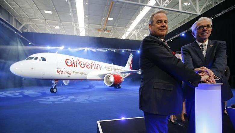James Hogan (L), CEO of Etihad Airways and Air Berlin's CEO Wolfgang Prock-Schauer pose in front of an aircraft following a news conference at Schoenefeld airport south of Berlin January 13, 2014. REUTERS/Fabrizio Bensch