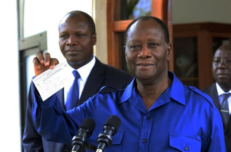 Ivory Coast President Alassane Ouattara shows his receipt to the media after filling out the census in Abidjan March 17, 2014. REUTERS/Thierry Gouegnon