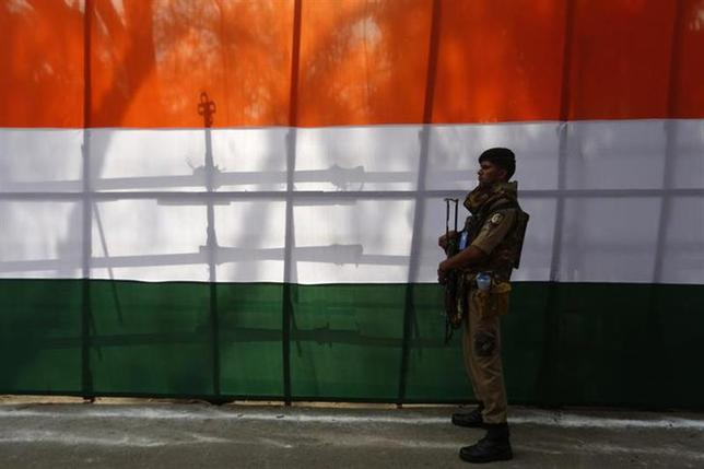 A security officer stands guard during the release of the Congress party's election manifesto for the April/May general election in New Delhi March 26, 2014. REUTERS/Adnan Abidi