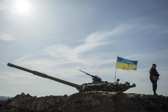 A soldier stands guard near a tank position close to the Russian border near the Ukranian city of Kharkiv March 24, 2014. U REUTERS/Dmitry Neymyrok