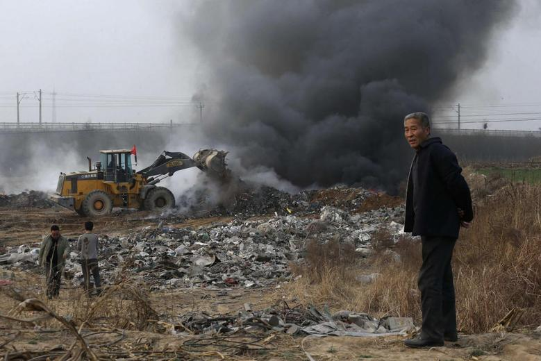 A man looks on as a bulldozer piles up garbage to burn on the outskirts of Baoding, Hebei province March 25, 2014. REUTERS/Stringer