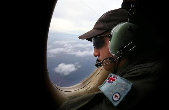 Airbourne Electronics Analyst Ben Herbert looks out an observation window from a Royal Australian Air Force (RAAF) AP-3C Orion aircraft while searching for the missing Malaysia Airlines Flight MH370 over the southern Indian Ocean March 26, 2014. REUTERS/Paul Kane/Pool