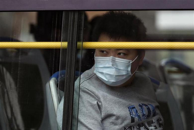 A man wearing a facial mask looks out from a window of a bus on a hazy day in Beijing March 27, 2014. REUTERS/Kim Kyung-Hoon
