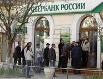 Очередь у отделения Сбербанка в Севастополе 24 марта 2014 года. Крупнейший госбанк РФ Сбербанк в 2013 году увеличил чистую прибыль, рассчитанную по международным стандартам, до 362,0 миллиарда рублей с 347,9 миллиарда рублей за 2012 год, говорится в сообщении банка. REUTERS/Vasily Fedosenko