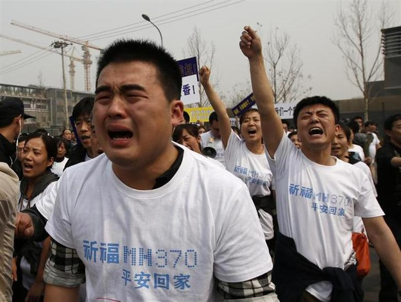 Family members of passengers onboard Malaysia Airlines MH370 cry as they shout slogans during a protest in front of the Malaysian embassy in Beijing March 25, 2014. REUTERS/Kim Kyung-Hoon
