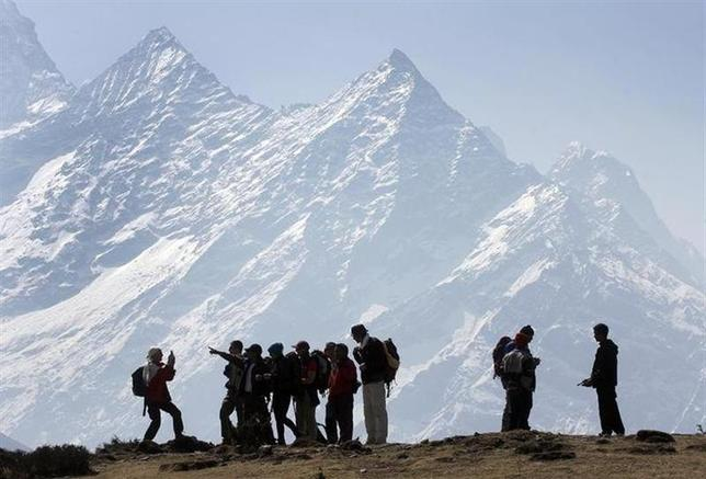 Trekkers pause to admire Mt. Kusum Kangru (6369 mts) in the Mt. Everest region in Nepal March 30, 2006. REUTERS/Gopal Chitrakar/Files