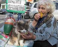 Женщина, просящая подаяния в центре Киева, кормит кота 29 апреля 2013 года. Миссия Международного валютного фонда согласовала с правительством Украины пакет реформ, в обмен на которые фонд даст переживающей тяжелый кризис и раскол стране $14-18 миллиардов, что откроет дорогу другим кредиторам и может довести объем помощи до $27 миллиардов в течение двух лет. REUTERS/Gleb Garanich
