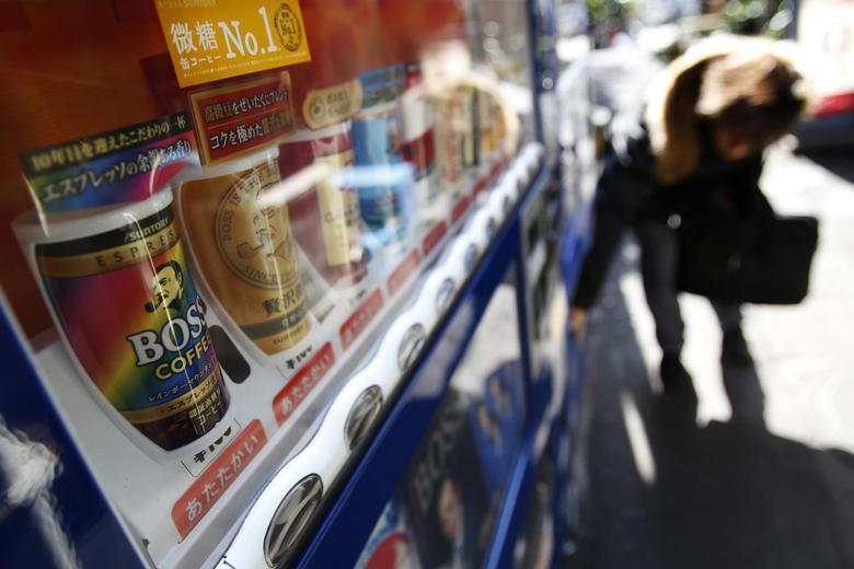 A man picks up a canned drink as ''Boss'' canned coffee, which are sold by Suntory Beverage & Food Ltd, are pictured inside a vending machine on a street in Tokyo February 17, 2014. REUTERS/Yuya Shino