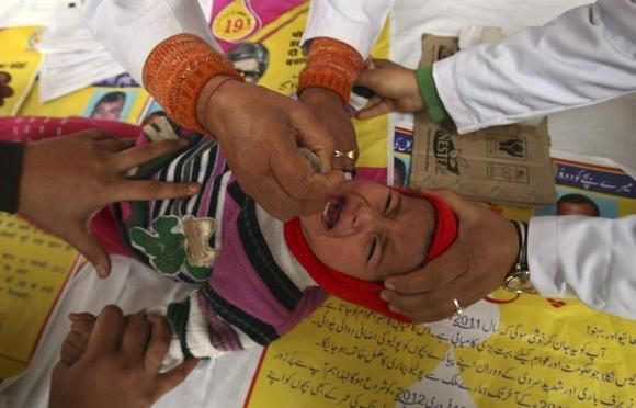 A child receives polio drops during a polio eradication programme in Jammu February 19, 2012. REUTERS/Mukesh Gupta/Files