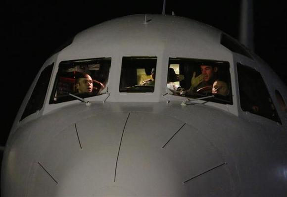 The cockpit crew of a Royal Australian Air Force (RAAF) AP-3C Orion are pictured upon their return to RAAF Base Pearce from a search for Malaysian Airlines flight MH370 over the southern Indian Ocean, March 26, 2014. REUTERS/Jason Reed