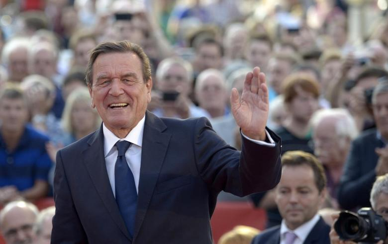 Former German Chancellor Gerhard Schroeder greets the audience as he supports Social Democratic top candidate Peer Steinbrueck (SPD) (not pictured) during an election campaign in Hanover, August 21, 2013. REUTERS/Fabian Bimmer