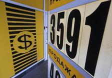 Вывеска пункта обмена валюты в Москве 20 февраля 2014 года. Рубль умеренно дешевеет вечером четверга, постепенно теряя поддержку экспортеров под занавес торговой сессии. REUTERS/Maxim Shemetov