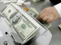 Um funcionário de um banco conta notas de cem dólares na sede do banco em Seul. O dólar chegou a recuar 2 por cento nesta quinta-feira, à casa dos 2,26 reais, após pesquisa mostrar queda na aprovação do governo da presidente Dilma Rousseff, num momento em que os mercados mostram ceticismo em relação à condução da política econômica do país. 24/02/2009 REUTERS/Jo Yong-Hak