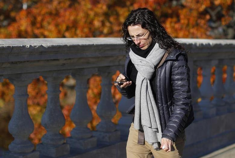 A woman looks down at her smart phone as she crosses the Weeks Footbridge in Cambridge, Massachusetts November 5, 2013. REUTERS/Brian Snyder