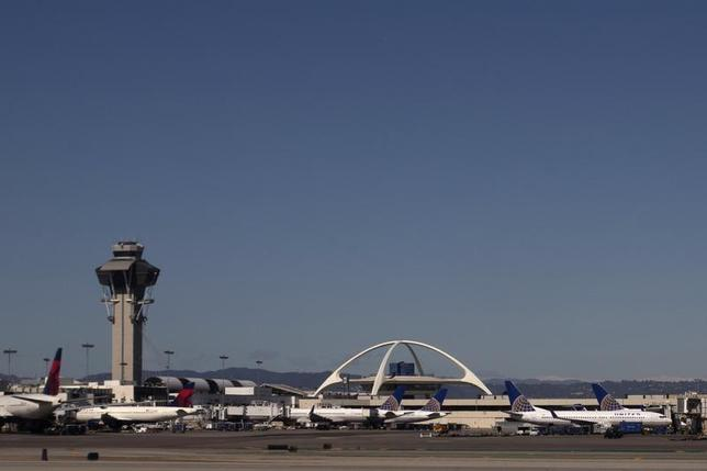Planes are seen in the foreground of the Los Angeles International Airport (LAX) and its air traffic control tower on February 20, 2013. REUTERS/Adrees Latif