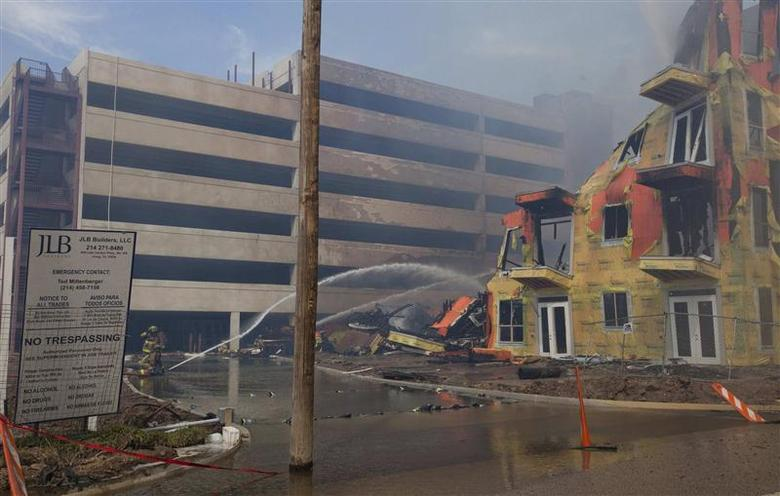 Firefighters work to extinguish a five-alarm blaze at a massive multi-story luxury apartment complex under construction in Houston March 25, 2014. REUTERS/Donna Carson