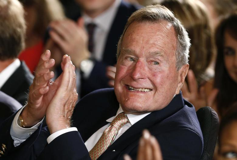 Former President George H. W. Bush applauds during an event to honor the winner of the 5,000th Daily Point of Light Award at the White House in Washington July 15, 2013 file photo. REUTERS/Kevin Lamarque