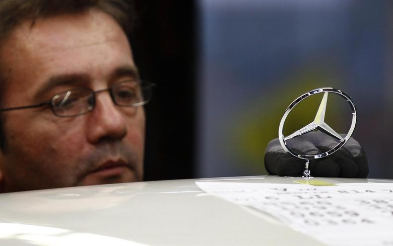 An employee adjusts an emblem on a German Mercedes-Benz S-class car at the plant in Sindelfingen near StuttgartJanuary 24, 2014. REUTERS/Michaela Rehle