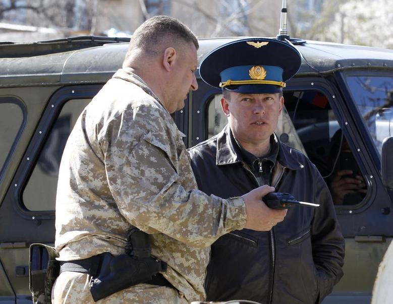 A Russian military officer (L) talks to Ukrainian Colonel Yuli Mamchur, demanding Ukrainian servicemen leave a military base in the Crimean town of Belbek near Sevastopol March 22, 2014. REUTERS/Vasily Fedosenko