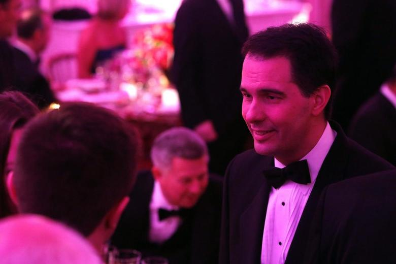 Wisconsin Governor Scott Walker (R-WI) (R) greets fellow guests before the 2014 Governors' Dinner in the State Dining Room of the White House in Washington, February 23, 2014 file photo. REUTERS/Jonathan Ernst