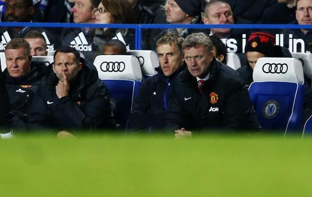 Manchester United manager David Moyes (R) watches from the bench with Phil Neville (2nd R) and Ryan Giggs (2nd L) during their English Premier League soccer match against Chelsea at Stamford Bridge in London, January 19, 2014. REUTERS/Eddie Keogh