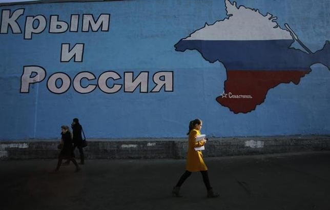 People walk past a mural showing a map of Crimea in the Russian national colours on a street in Moscow March 25, 2014. The mural reads: ''Crimea and Russia''. REUTERS/Artur Bainozarov