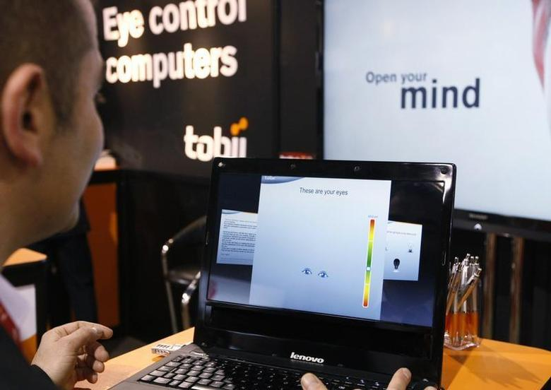 A Tobii Technology representative demonstrates what the Swedish company says is the world's first first eye-controlled laptop at the Consumer Electronics Show in Las Vegas January 11, 2012. REUTERS/Rick Wilking