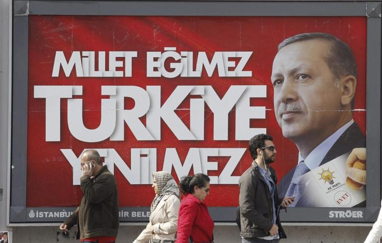 People walk past a poster for Turkey's Prime Minister Tayyip Erdogan's election campaign in Istanbul March 27, 2014. REUTERS/Osman Orsal/Files