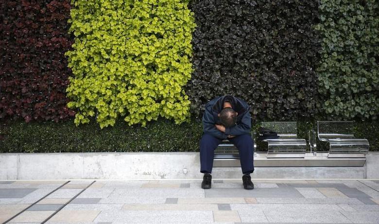 A man takes a nap at a bench at a street in Tokyo November 29, 2013. REUTERS/Yuya Shino